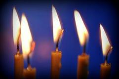 Tända stearinljus på en blå bakgrund royaltyfri fotografi