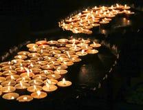 tända stearinljus på mass i kyrka arkivbild