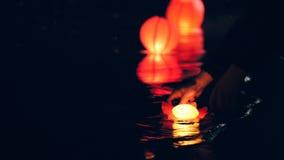 Tända sväva belysninglyktor på floden på natten - romantisk festival royaltyfri fotografi