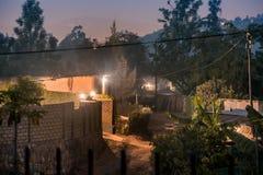 Tände dunkelt gataplats bland hus i Nyamirambo, ett avsides s royaltyfri foto