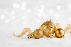 Tänder guld- bollar för jul på snö över abstrakt vinter bakgrund arkivfoto