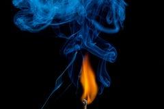 Tändning av matchen med röker Royaltyfri Foto