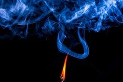 Tändning av matchen med röker Royaltyfri Bild