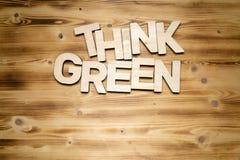 TÄNK GRÖNA ord som göras av träkvarterbokstäver på träbräde royaltyfri foto