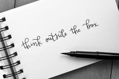 TÄNK UTANFÖR ASKEN som hand-märkas i notepad med borstepennan royaltyfri fotografi