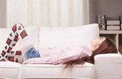 Tänka eller sova den nätta flickan på hennes soffa arkivfoto