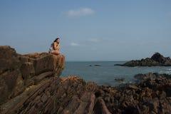 Tänka om evighet överst av havsreven Den vita kvinnan mediterar överst av en klippa Royaltyfri Foto