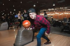 Tänka ut en ung man som går att kasta en boll för att bowla Student som spelar bowling En blick på kameran Arkivfoton