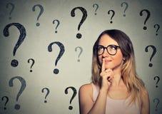 Tänkande affärskvinna med exponeringsglas som ser upp på fläcken för många frågor royaltyfri fotografi