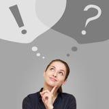 Tänkande affärskvinna som ser upp på fråge- och utroptecken Fotografering för Bildbyråer