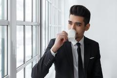 Tänkande affärsman i dräktsammanträde på fönsterbräda- och drinkkaffe Arkivfoton