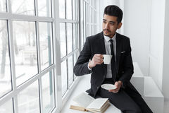 Tänkande affärsman i dräktsammanträde på fönsterbräda- och drinkkaffe Fotografering för Bildbyråer