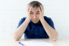 Tänkande affärsman som trycker på hans huvud som rymmer ett dokument som sitter på tabellen en man i affärskläder som sitter på t fotografering för bildbyråer