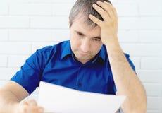 Tänkande affärsman som trycker på hans huvud som rymmer ett dokument som sitter på tabellen en man i affärskläder som sitter på t arkivfoto