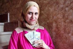 Tänkande arabisk muslimkvinna med pengar Royaltyfria Bilder