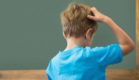 Tänkande elev som skrapar hans huvud i klassrum royaltyfri foto