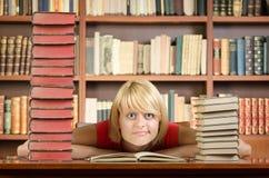 Tänkande flicka på arkivtabellen med gruppen av böcker runt om henne fotografering för bildbyråer