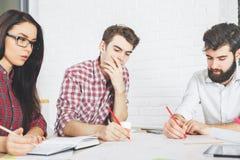 Tänkande folk som gör skrivbordsarbete och att använda apparater Arkivbild
