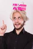 Tänkande grabb med den rosa gåvaasken på hans huvud fotografering för bildbyråer