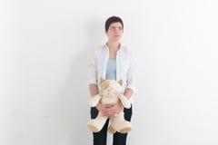 Tänkande kvinna som grubblar över något, tillfällig ung härlig caucasian kvinna i den vita skjortan som håller katten i henne Royaltyfri Foto