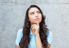 Tänkande latin - amerikansk kvinna med långt hår som är utomhus- i summen arkivfoto