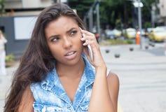 Tänkande latin - den amerikanska kvinnan i jeans klår upp på telefonen Arkivbild