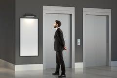 Tänkande man i rum med elevatorn Arkivbild