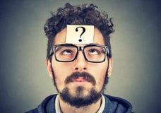 Tänkande man med frågefläcken som ser upp Arkivfoton