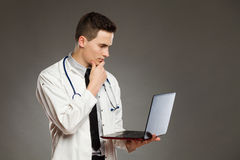 Tänkande manlig doktor med bärbara datorn Royaltyfria Bilder