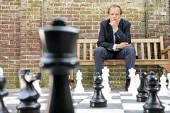 Tänkande mansammanträde på ett liv storleksanpassade det utomhus- schackbrädet Fotografering för Bildbyråer
