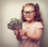 Tänkande rolig liten ungeflicka i exponeringsglas som räknar pengar i hanen Arkivbilder