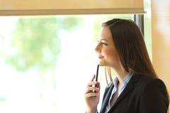 Tänkande se för affärskvinna till och med ett fönster royaltyfria bilder