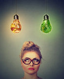 Tänkande se för kvinna upp på skräpmat- och gräsplangrönsaker som formas som ljus kula ovanför huvudet Royaltyfri Bild