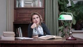 Tänkande sittnig för allvarlig kvinna på arbetsskrivbordet med böcker lager videofilmer