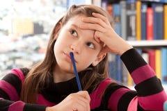 Tänkande stunder för flicka som gör läxa arkivfoton