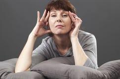 Tänkande 50-talkvinna som lyfter henne ögon för mjuk ansikts- kontur Arkivfoton