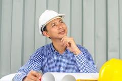 Tänkande ung man för Asien teknikerleende och som ser bort, medan sitta på behållareaskbakgrund Royaltyfri Foto