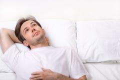 Tänkande ung man som ligger på säng Royaltyfri Bild
