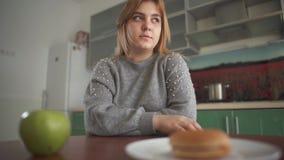 Tänker den knubbiga flickan för ståenden att hon bör äta en smaklig hamburgare eller ett saftigt grönt äpple Svårt val mellan stock video
