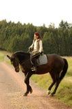 Tänzelndes Pferd und Horsewoman mit Blumen. Stockbild