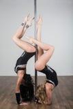 Tänzer, der akrobatische Tricks mit einem Pfosten tut Stockbilder