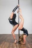 Tänzer, der akrobatische Tricks mit einem Pfosten tut Lizenzfreie Stockbilder