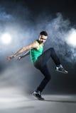 Tänzer, der auf Hintergrund mit Blitzen und Rauche aufwirft Lizenzfreie Stockfotografie