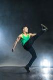 Tänzer, der auf Hintergrund mit Blitzen und Rauche aufwirft Lizenzfreies Stockbild