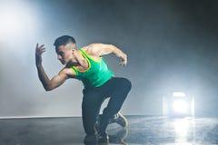 Tänzer, der auf Hintergrund mit Blitzen und Rauche aufwirft Stockbild