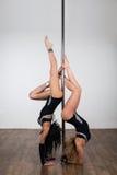 Tänzer, der schwierige akrobatische Tricks mit einem Pfosten tut Lizenzfreie Stockbilder