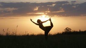 Tänzer-Yogahaltung des Schattenbildes der jungen Frau hereinkommende vor schönem Sonnenuntergang, Fruska-gora, Novi Sad, Serbien