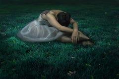 Tänzerfrau, die auf Nachtgrasszene sitzt Lizenzfreies Stockfoto