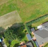Täppor med en äng, en gräsmatta, en småhus och ett terrasserat hus gränsa till varandra på en punkt, täppagränser ser som abstrak Arkivbilder