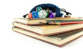 Tärning och blyertspennor överst av böcker Arkivbilder